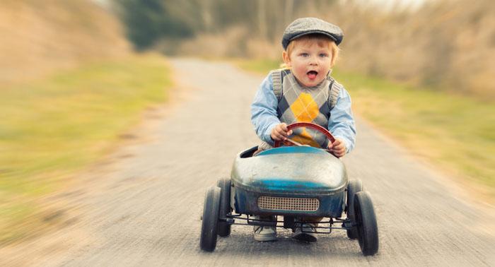 kleiner Junge im Kettcar